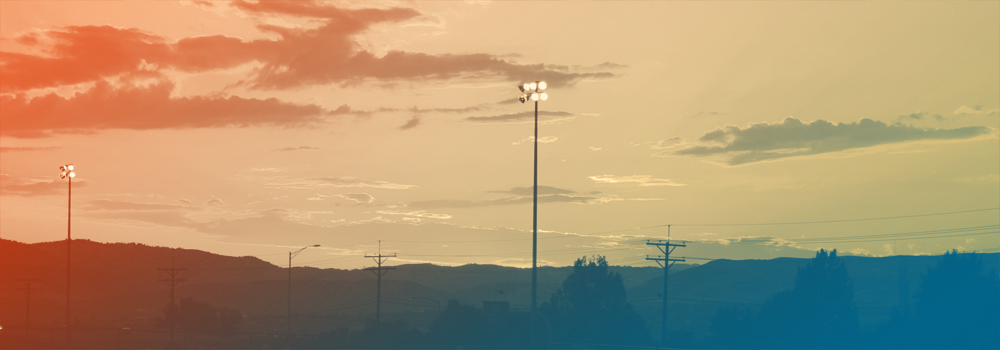 View of a sunset with athletic field floodlights in Denver, Colorado