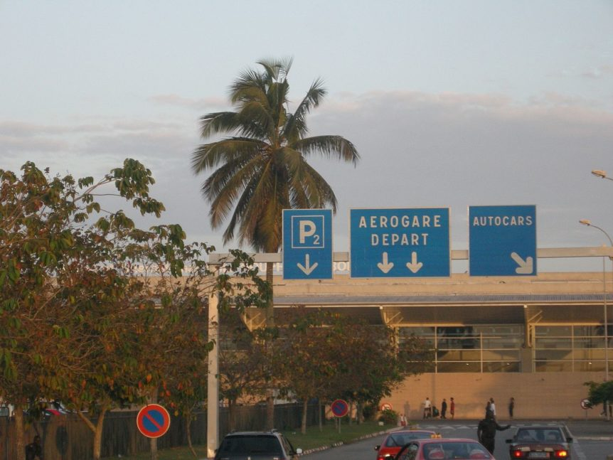 """Photograph of palm tree signs reading """"P2 / Aerogare Deaprt / Autocars"""" outside an airport terminal"""